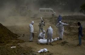 नई दिल्ली में कोविड-19 से मरे व्यक्ति को दफनाते हुए लोग